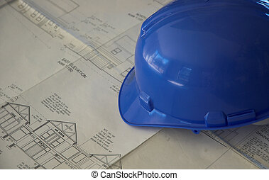 Hard hat and building plans - Blue hard hat on white...