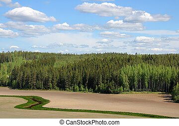 Agricultural landscape with cultivated fields, forest, river...