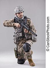 Kneeling Soldier with machine gun in studio