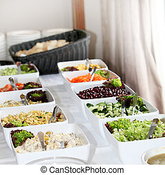 Salad buffet at a catered function with rows of square...