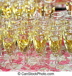 Full champagne flutes on a table ready to be served at a...