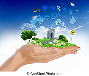 Human hand holding a green landscape - Collage with a human...