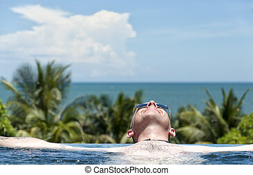 Chilled in paradise - A handsome adult male lies chilled in...