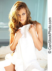 Flirt - Posh young woman with sheet looking at camera