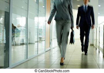 Walking down corridor - Businesspeople going along corridor...