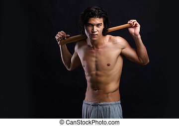 Sportsman - Image of shirtless man with bat looking at...