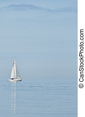 Lone Yacht - A lone yacht heads out to open sea against a...
