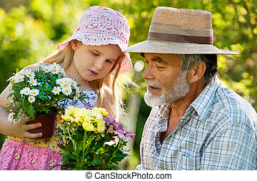 Gardening - Happy grandfather with his granddaughter working...