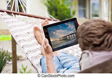 Man using a tablet computer while relaxing in a hammock
