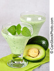 avocado smoothie - Two glasses of avocado smoothie with...