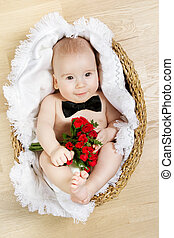 adorable baby holding flowers and wearing butterfly tie, lying in basket. Young gentleman concept.