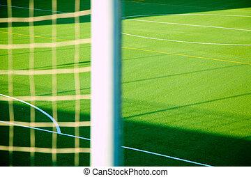 Green soccer net detail with sport grass field
