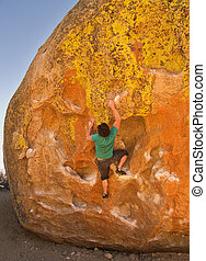 Man Rock Climbing - man rock climbing on a large boulder at...