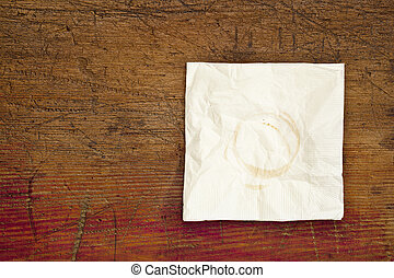 napkin with coffee stains on a grunge scratched wooden table