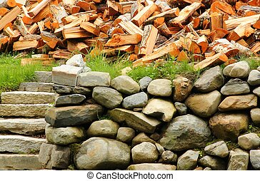 woodpile above a rock wall