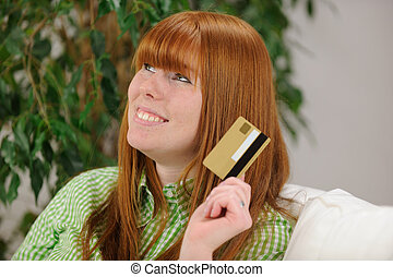 young woman with credit card smiling