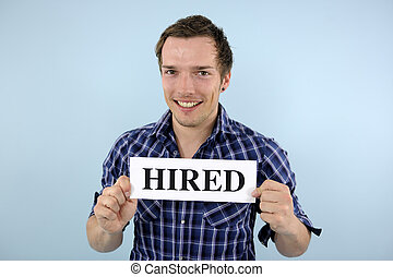 young man holding hired sign - happy young man holding hired...