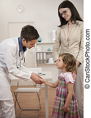 Pediatrician shaking hand with girl child patient at office