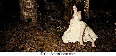 Bride in dark woods - A bride sitting beneath a tree in dark...