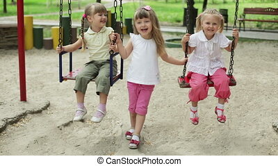 Three girls laughing child on a swi