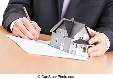 Real estate concept - business man signs contract behind home architectural model