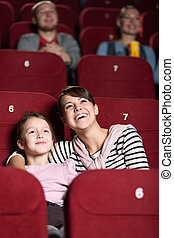 Young girl in the movie - Young with her mother watching a...