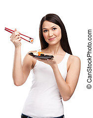 Attractive woman holding sushi roll with a chopsticks