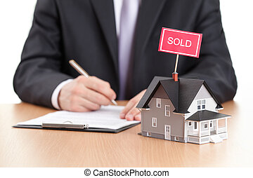 Business man signs contract behind home architectural model