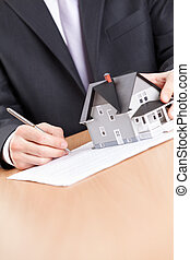 Business man signs contract behind house architectural model