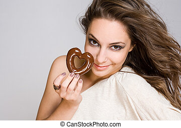 Brunette beauty with heart shaped chocolate. - Portrait of a...