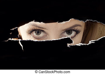 Womens eyes spying through a hole close up
