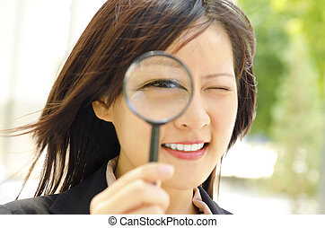 I am watching you - Asian business woman with magnifying...