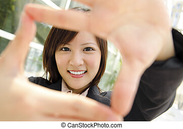 Vision - Smiling Asian business woman making a frame with...