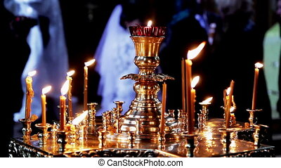 Orthodox believers - Many candles are lit next to the...