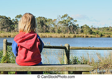 Lonely girl on bench - Lonely little blonde girl sitting on...