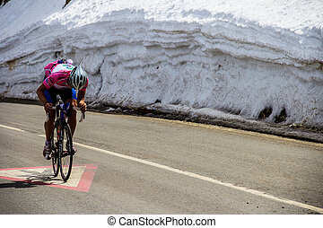 Cyclist cycling up a road next to a wall of snow