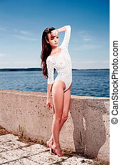 High fashion look.glamour portrait of beautiful sexy brunette female model girl in white lingerie outdoors .blue sky.walking near sea