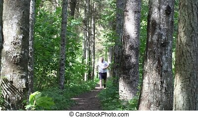 Man running along the forest trail