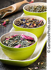 Mix of dry green and flower tea in bamboo bowls