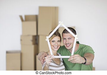 Young couple moving in new home - happy Young couple moving...