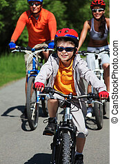 Outdoor activity - Portrait of happy boy riding bicycle in...
