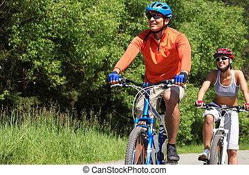 Cycle race - A young couple racing on bicycles in natural...