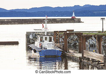 Pilot Boat at Dusk - A pilot boat docked near a seawall and...