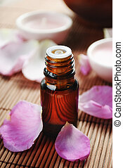 Spa treatment - Essential oil with rose petals on wooden...