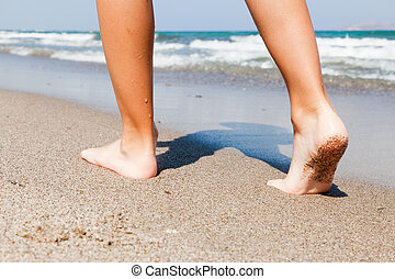 Woman walking on beach - Woman walking barefoot on sunny...