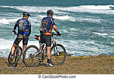 Two cyclists on sea beach