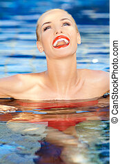 Laughing woman relaxing in a pool