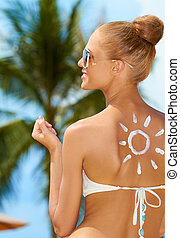 Smiling woman with the sun painted on her back