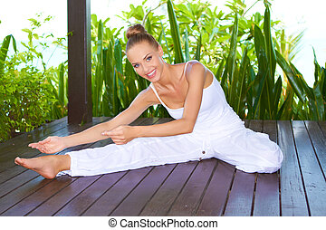 Woman stretching as she practices yoga