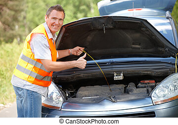Oil level check - Man checking level of oil on a car engine...